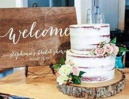 wooden welcome sign next to a cake