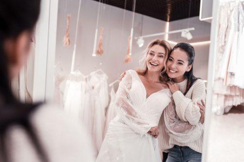 a bride admiring her wedding dress in the mirror
