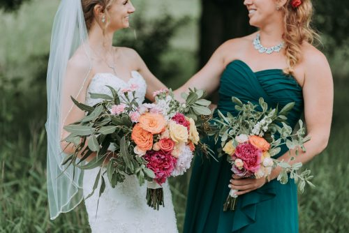 bride and maid of honor smiling at each other
