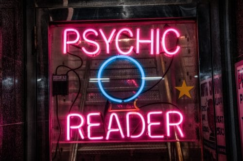 """neon sign that says """"psychic reader"""""""